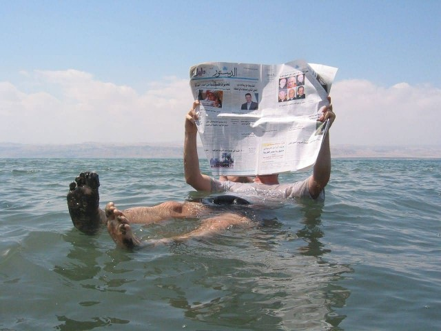 A Man Reading A Newspaper In The Dead Sea